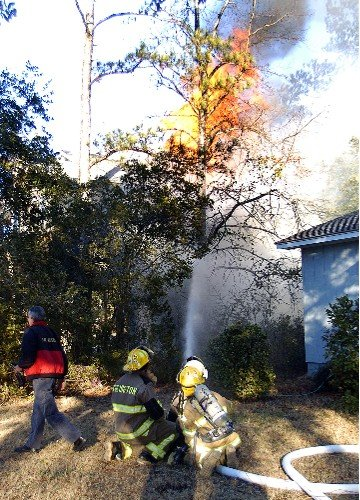 Colington firefighters battle a one-alarm blaze on Baum Bay Drive in Colington on Monday evening, January 17, 2005. The fire, which severly damaged the house, started outside the house in a trash can, according to neighbors. Fire officials were still investigation the blaze into the night. (Photo by Joshua Corsa)